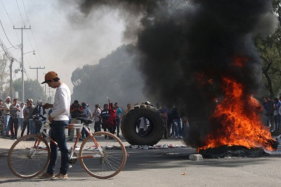 Protesters block the entrance to Pemex gas station as they burn tires during a protest against the rising prices of gasoline enforced by the Mexican government in San Miguel Totolcingo